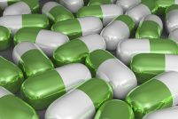 White and green pills lying close to each other, close up
