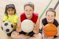 A multi-ethnic group of elementary age children are sitting on a gym floor indoors, each are holding a sports ball, and they are smiling and looking up at the camera.