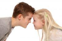 Das Foto zeigt ein Geschwisterpärchen, welches Kopf an Kopf ist und sich böse anschaut.