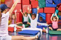 Gruppe Kinder beim Kinderturnen in der Vorschule mit Sportlehrer